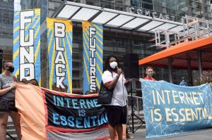 Devren Washington, Senior Policy Organizer at MAP, stands in front of several banners at an rally to demand internet access.