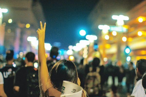 Image of protestor holding a peace sign.